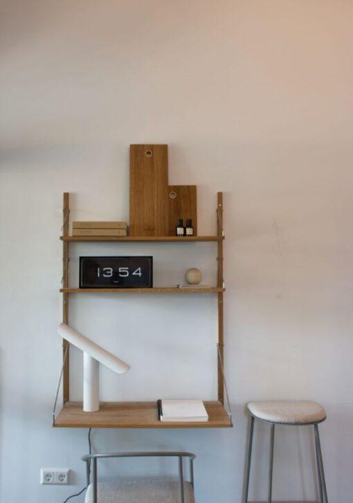 překlápěcí hodiny Brick v černé barvě na dřevěné polici